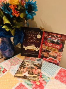 Photos of 3 of my themed cookbooks, against a backdrop of colorful place-mats and flowers.